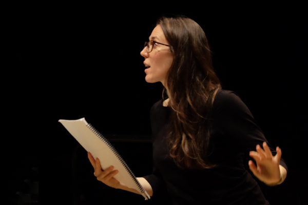 A woman with long hair and glasses holding a musical score and gesturing energetically