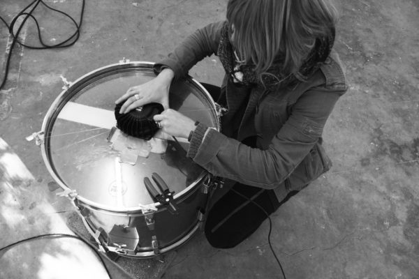 A woman wiring a bass shaker on a large drum seen from above