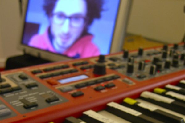 A red synthesizer keyboard with a man's face visible out of focus on a screen in the background