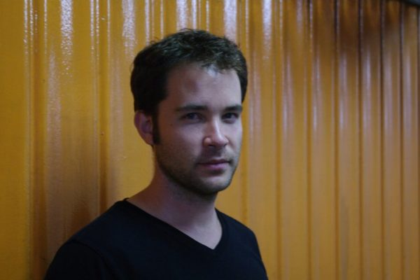 A man with stubble and dark hair looking directly into the camera against a mustard-colored wall