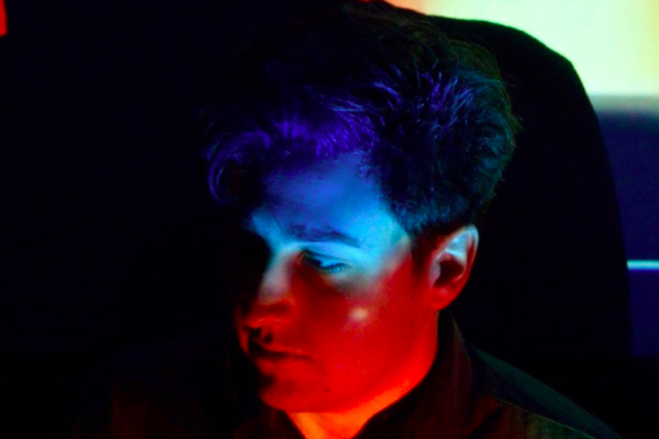 A man illuminated by lights of different colors looking down to his right