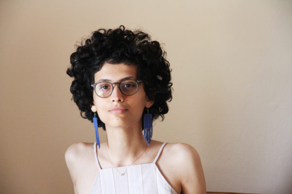 A woman with curly hair, glasses, and big, blue earrings stares into the camera