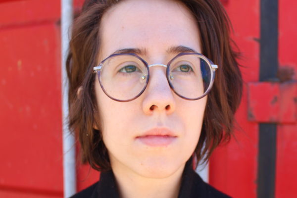 A woman with glasses and short hair stares at the distance pensively against a red background
